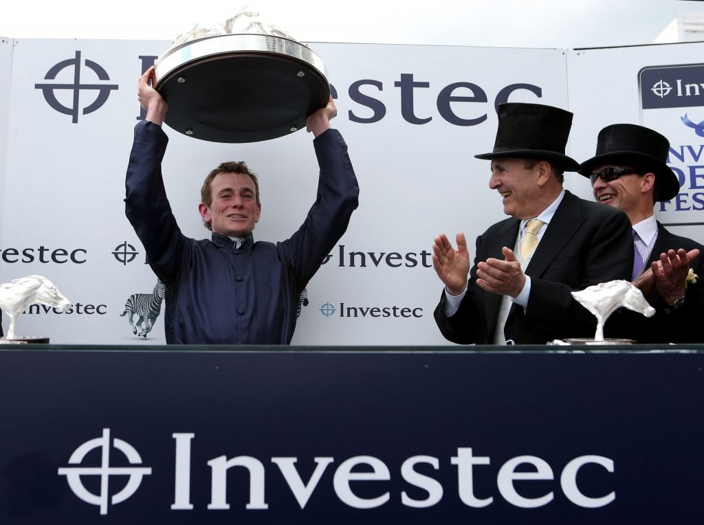 Ryan Moore celebrates with the trophy after winning The Investec Derby onboard Ruler of the World