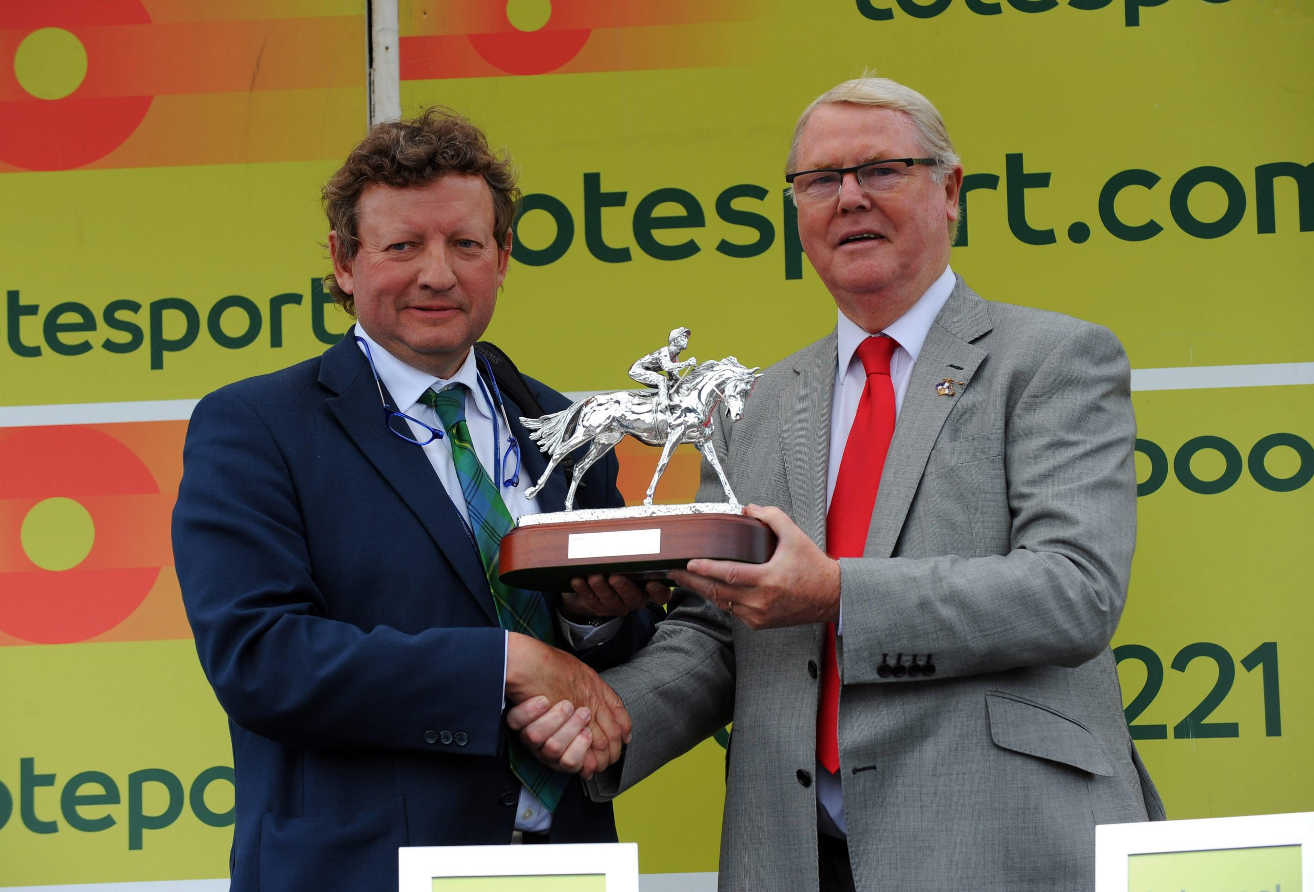 Trainer Mark Johnson (left) receives the trophy after victory with Dordogne in the totesport.com Derby Trial Stakes